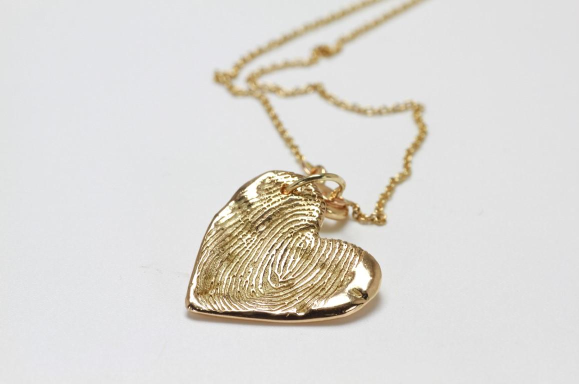 Vingerafdruk op gouden hart hanger